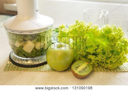 Cooking of green smoothie cocktail in a blender. Still Life with a blender fruit and herbs on the table. The concept of a healthy lifestyle.