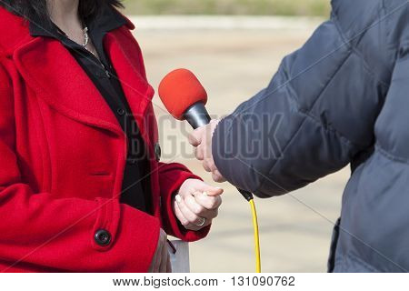 Journalist holding a microphone conducting TV or radio interview