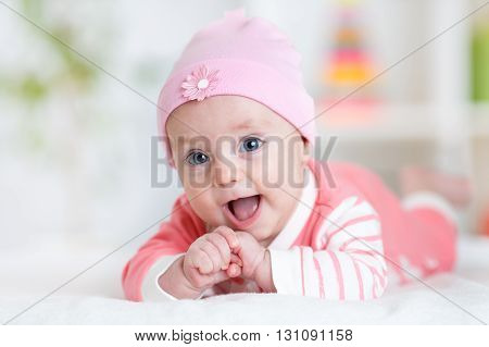 Cute baby girl. Smiling child lying on white bed in nursery room