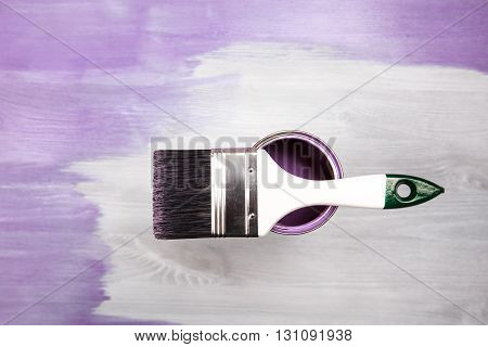 Paintbrush and can with lavender color lying on white wooden background. The surface is half - toned with violette color.