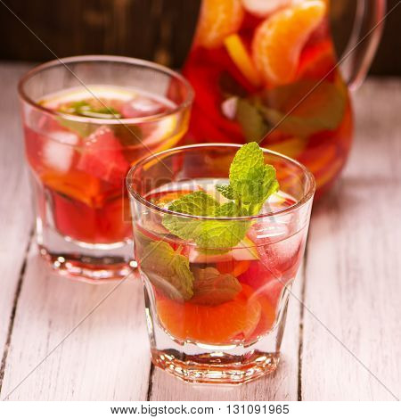 Sangria with fruits and mint leaves in glasses over wooden background. Selective focus