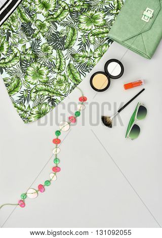Woman essentials. Fashion lady summer outfit, girl clothes set, cosmetics, makeup accessories. Stylish handbag clutch, green dress, necklace, sunglasses. Unusual overhead, top view on gray