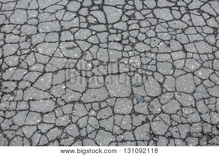 Old worn and cracked asphalt with cracks.