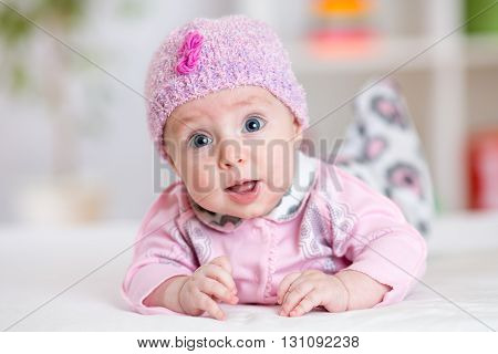 Funny baby girl. Small child lying on white bed in nursery room