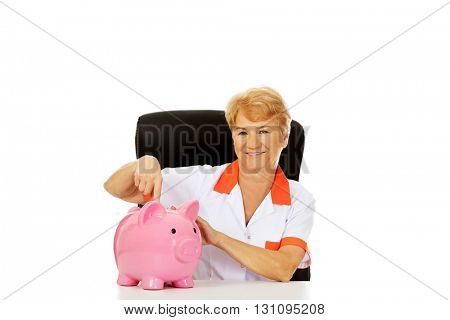 Smile elderly female doctor or nurse sitting behind the desk wit piggybank