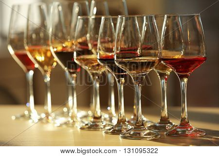 Many glasses of different wine in a row on a table
