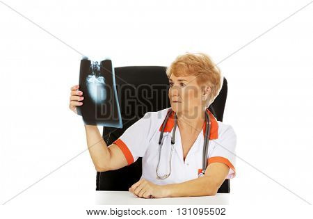 Pensive elderly female doctor looking for x-ray photo