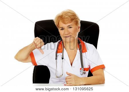 Elderly female doctor or nurse sitting behind the desk and shows thumb down