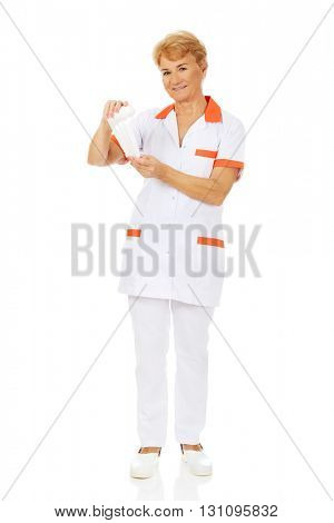 Smile elderly female doctor or nurse holds bandage