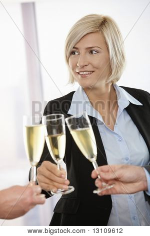Happy young businesswoman celebrating success with champagne at office, smiling.