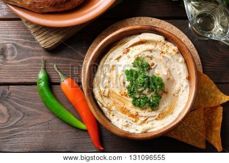 Wooden bowl of tasty hummus with chips and parsley on table
