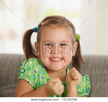 Portrait of excited little girl (3-4 years) at home.?