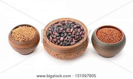 Pots with beans, rice and lentils isolated on white background