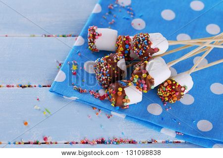 Tasty marshmallows with chocolate on sticks, close up
