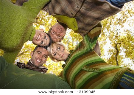 Happy friends standing with their heads together in autumn forest, smiling. Low angle view.?
