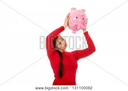 Happy young woman shaking piggybank