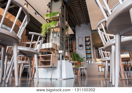 Low angle of wooden tables and chair in restaurant. Green plants create cozy atmosphere
