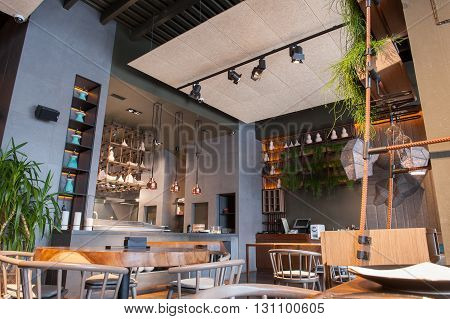 Cozy atmosphere of modern restaurant with wooden tables and chairs