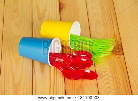Bright plastic disposable tableware on a background of light wood.