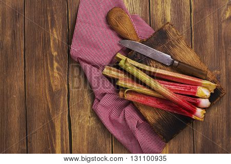 Fresh rhubarb on wooden cutting board. Rustic style, selective focus. Top view