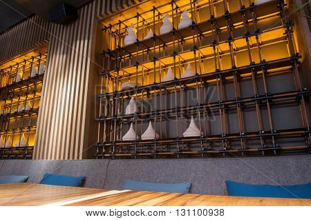 Modern restaurant with wooden table and decorative utensil on shelf at wall