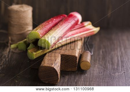 Fresh rhubarb on wooden cutting board. Rustic style, selective focus
