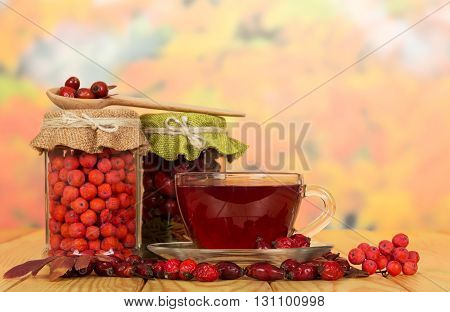 Banks with berries of mountain ash, wild rose and cup of tea on a background of autumn leaves.
