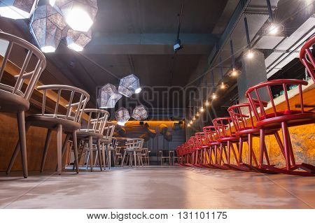 Low angle of elegant restaurant with colored chairs and wooden tables