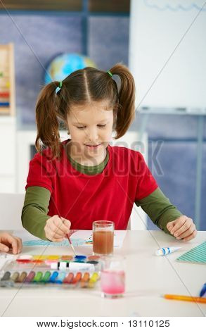 Elementary age girl sitting at desk enjoying painting with colors in art class at primary school classroom, smiling.?