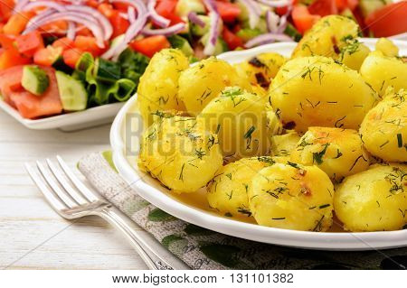 Roasted young potatoes with garlic and dill on wooden background.