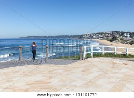 A women enjoys the view from a lookout over Bar Beach and Merewether Beach - Newcastle Australia. Newcastle is a popular destination with many beautiful beaches.