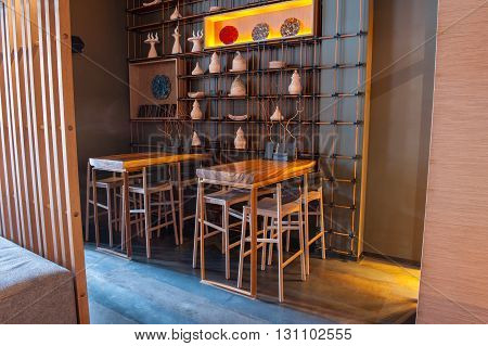 Modern wooden tables with chairs and special decoration create cozy atmosphere in restaurant