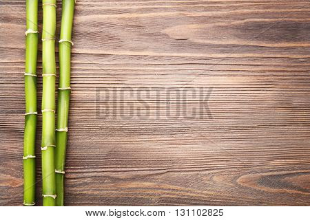 Bamboo branches on wooden background