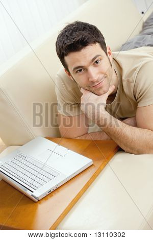 Happy young man laying on sofa at home using laptop computer, smiling. High-angle view.