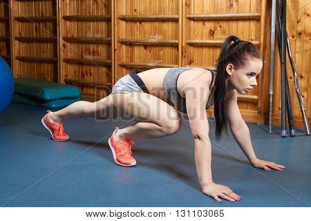 Young and beautiful body builder warming-up her legs in the gym