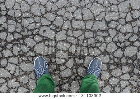 Gumshoes on urban grunge background of cracked asphalt. Conceptual image of legs in boots on city. Feet shoes walking in outdoor. Youth Selphie Modern hipster.