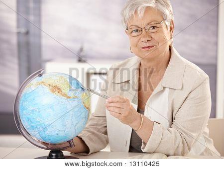 Oberlehrer am Schreibtisch sitzend auf Kugel, lehrt Geographie in der Grundschule.?