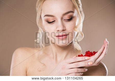 Close-up Portrait Of Blonde With Red Pills In Hands