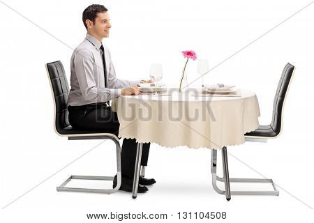 Young man sitting at a restaurant table and waiting for his date isolated on white background