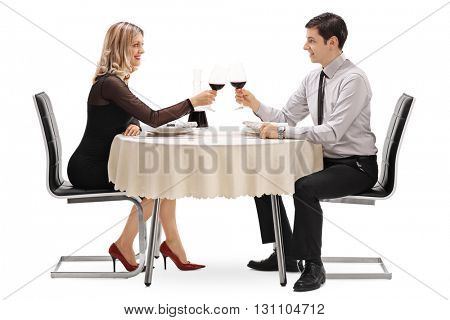 Young man and woman drinking red wine on a romantic date isolated on white background