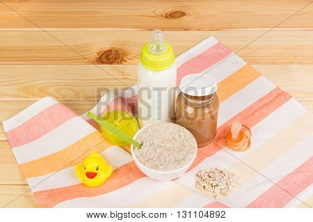 A bottle of milk, a bowl of oatmeal, mashed potatoes, nipple and rubber duck on a background of light wood.