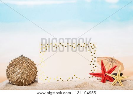 Blank card, starfish and Christmas toys in the sand on the seashore.