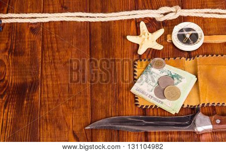 Old, compass, money, a knife and a starfish on a background of dark wood.