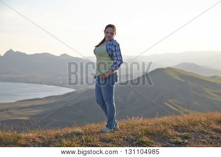 Woman traveler looks at the edge of the cliff on the  sea bay of mountains in the background