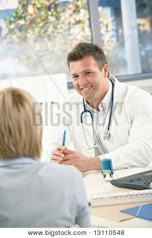 Smiling medical doctor consulting patient in bright office.?