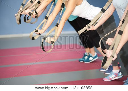 Close up of arms of young women doing push-ups with trx equipment. They are stretching and leaning hands on straps