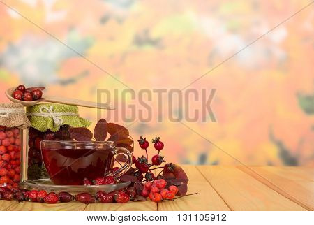 Glass jars with rose hips, mountain ash berries and a cup of tea on a background of autumn leaves.