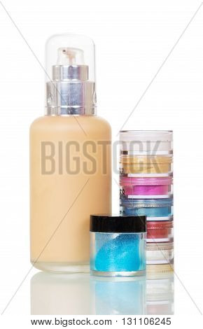 Bright eye shadows and liquid foundation makeup isolated on white background.