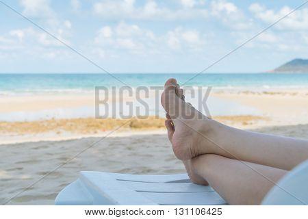 Woman leg on tropical sea beach