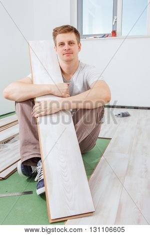 Worker sits smiling with a light laminate plank